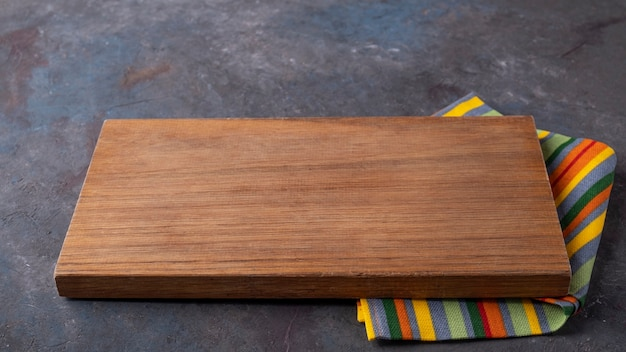 Empty wooden board with color napkin