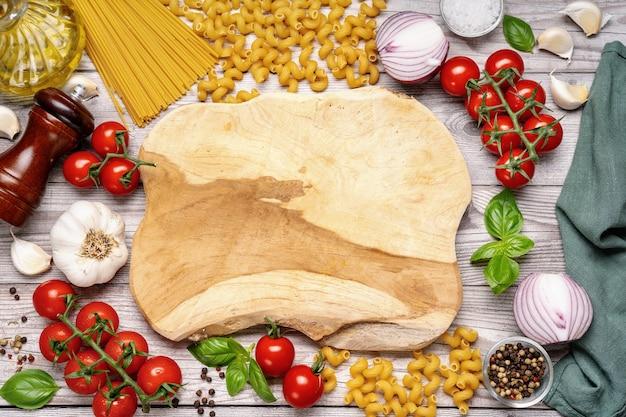 Пустая деревянная доска с овощами вокруг на деревянном столе. таблица здорового вегетарианского питания. макет. скопируйте пространство. вид сверху