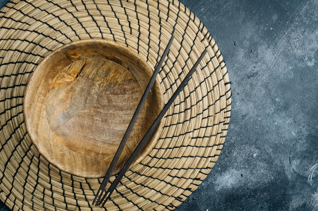Empty wooden bowl (empty bamboo bowl) with chinese chopsticks on gray stone. asian food concept