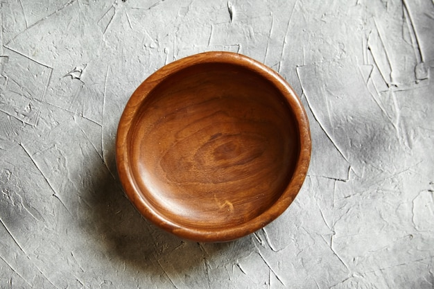 Empty wooden bowl on grey background. single round salad bowl on concrete table, top view