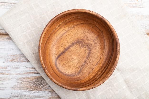 흰색 나무 배경 및 리넨 섬유에 빈 나무 그릇. 평면도, 평면 누워, 닫습니다.