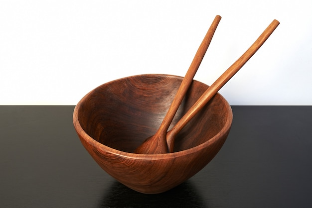Empty wooden bowl with spoon and fork