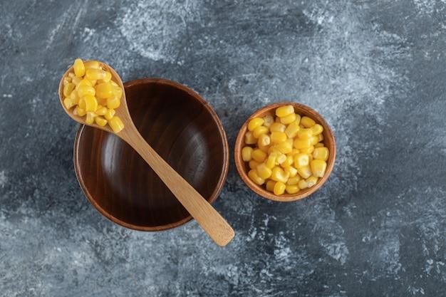 Una ciotola di legno vuota con un cucchiaio di legno di semi di popcorn.