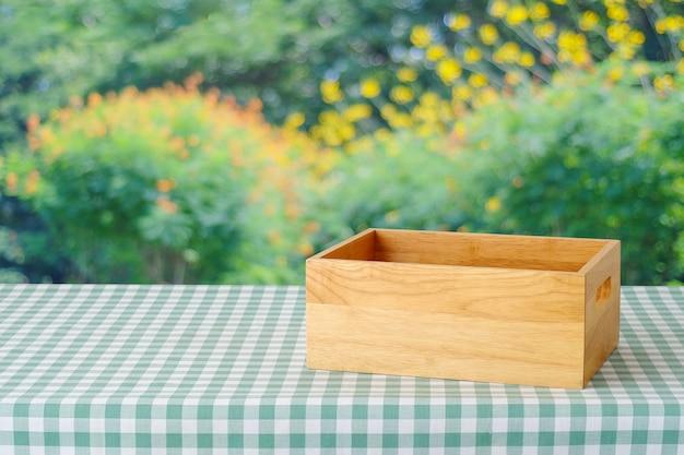 Bokeh 빛을 배경으로 흐림 나무, 제품 디스플레이 몽타주 위에 녹색 스콧 패턴 식탁보와 테이블에 빈 나무 상자