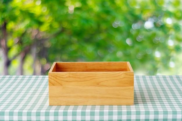 녹색 스콧 패턴 식탁보와 테이블에 빈 나무 상자