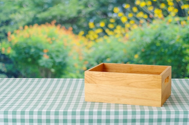 Empty wooden box on table with green scott pattern tablecloth over blur tree with bokeh light background, product display montage