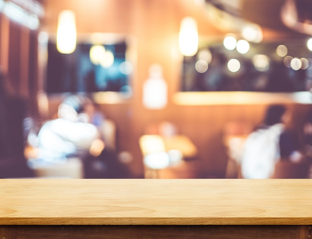 Empty wooden brown table top at blur restaurant background with bokeh light