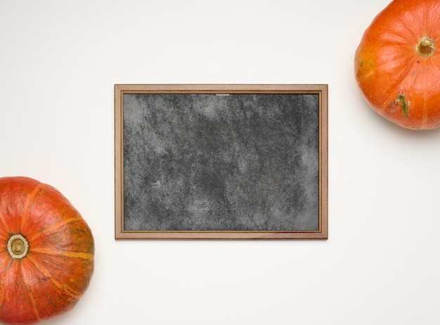 Empty wooden chalk frame and round ripe orange pumpkins on white background, top view, copy space