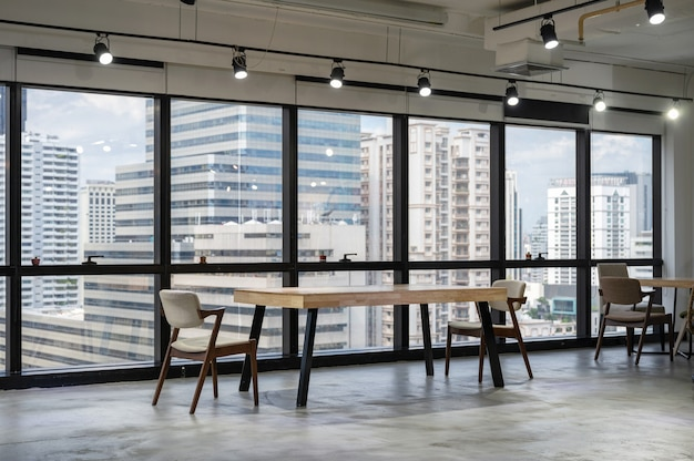 Empty wooden conference table with chairs in coworking space on downtown