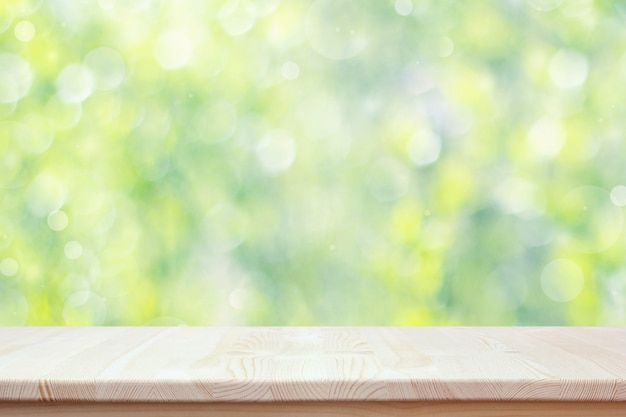 Empty wooden countertop on blurred spring background with bokeh.
