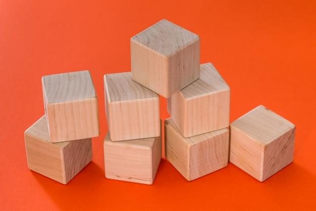 オレンジ色の背景に分離された空の木製キューブブロック