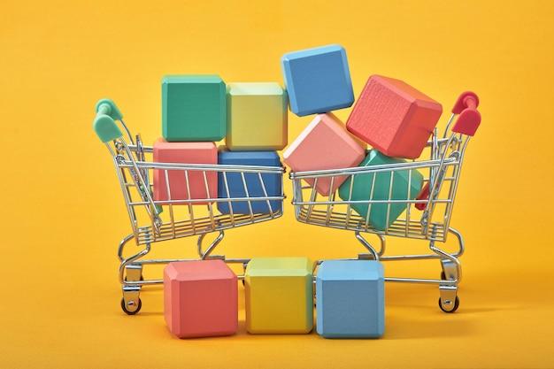 空の木製の立方体のモックアップスタイル、黄色の背景にショッピングカートでスペースをコピーします。創造的なデザインのためのカラフルなブロックテンプレート、テキストのための場所。
