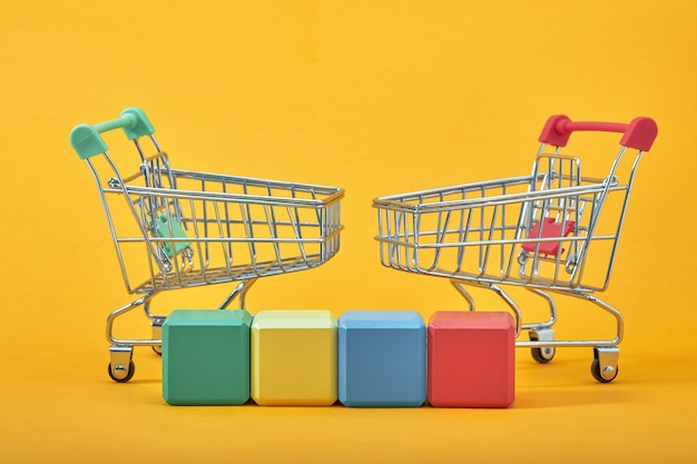 Пустые деревянные кубики в стиле макета, копия пространства с тележками для покупок на желтом фоне