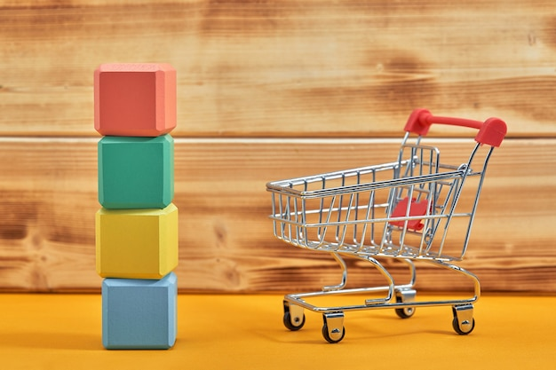 Empty wooden cubes mockup style, copy space with shopping trolleys on wooden surface