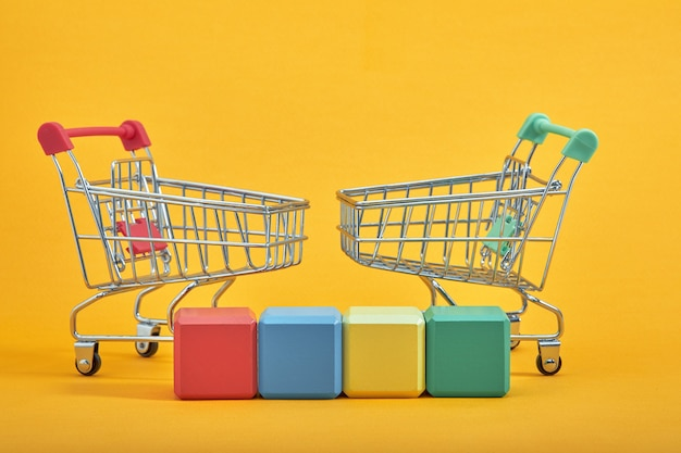 Empty wooden cubes mockup style, copy space with shopping trolleys on yellow background. colourful blocks template for creative design, place for text.