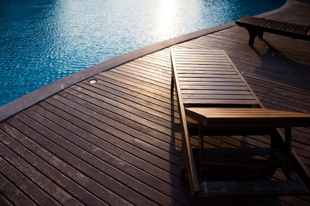 Empty wooden deck and chair with swimming pool