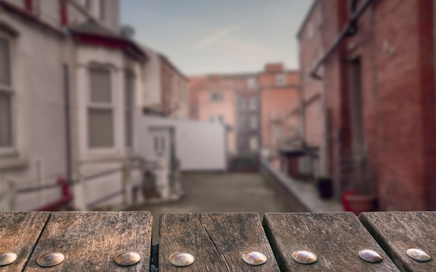 Empty wooden deck table on blurry alley background. can be used for mockup products displays