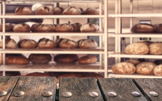 Таблица пустая деревянная палуба на расплывчатой предпосылке пекарни. может использоваться для демонстрации макетов продуктов