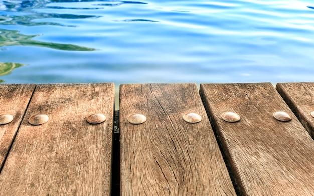 ぼやけた川の背景に空のウッドデッキテーブル。モックアップ製品のディスプレイに使用できます