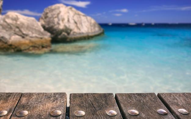 ぼやけた海と空の背景に空の木製デッキテーブル。モックアップ製品のディスプレイに使用できます