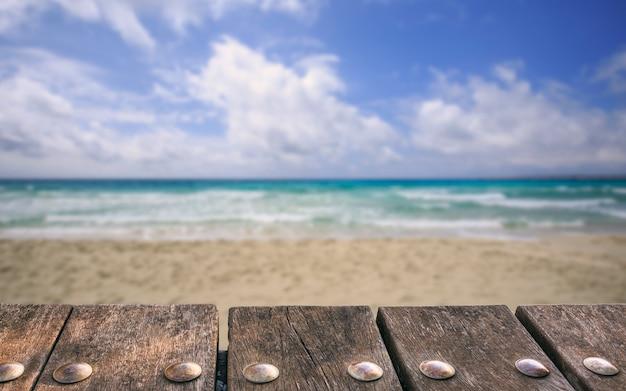 Пустая деревянная таблица палубы на расплывчатой предпосылке моря и неба. может использоваться для демонстрации макетов продуктов