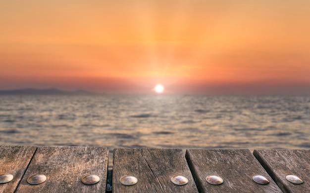 ぼやけた夕日の背景に空のウッドデッキテーブル。モックアップ製品のディスプレイに使用できます