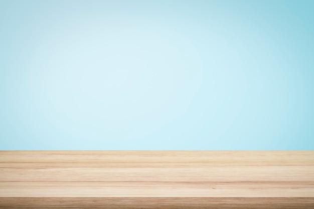 현재 제품에 대 한 밝은 파란색 벽지 배경 위에 빈 나무 데크 테이블.
