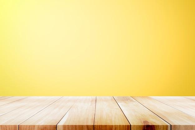 노란색 바탕 화면 배경 위에 빈 나무 데크 테이블입니다.