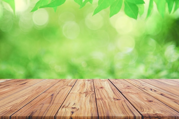 Empty wooden deck table top on green blurred abstract background from foliage background