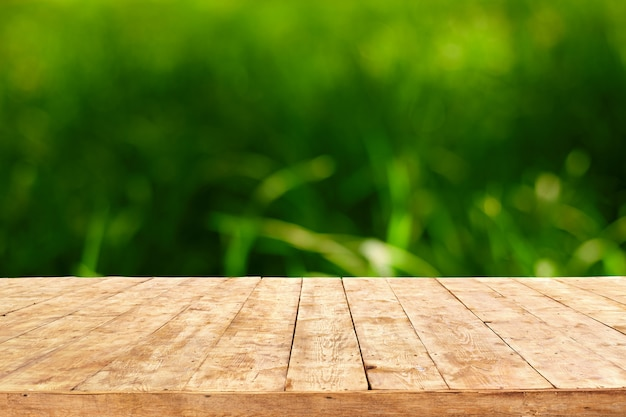 Empty wooden deck table with foliage bokeh background. ready for product display montage.