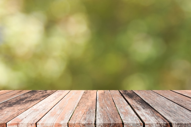 Empty wooden deck table with foliage bokeh background. ready for product display montage
