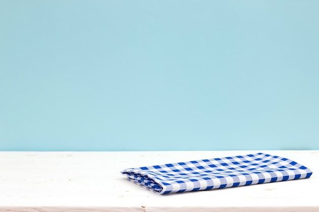 Empty wooden deck table with tablecloth over pastel blue background