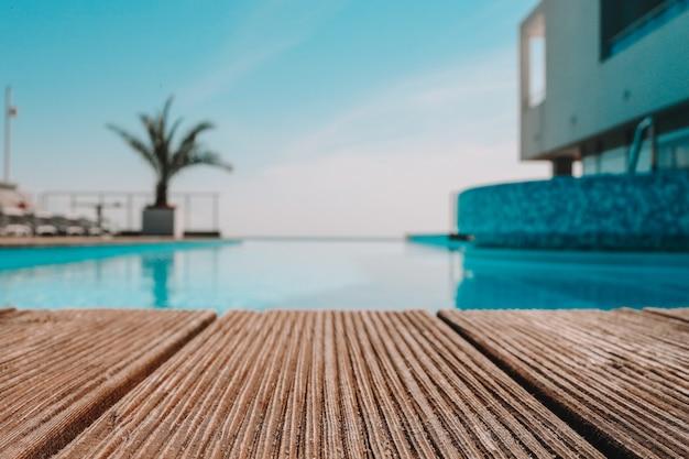Пустая деревянная палуба с бассейном, красивый минималистский вид на бассейн с ясным голубым небом. применяется винтажный цвет фильтра