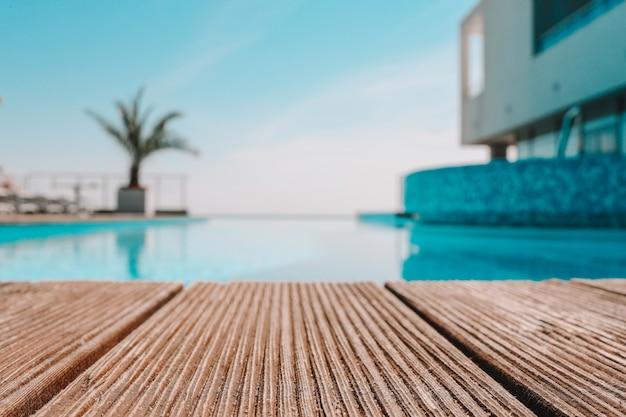 Пустая деревянная палуба с бассейном, красивый минималистский вид сбоку на бассейн с ясным голубым небом. применяется винтажный цвет фильтра