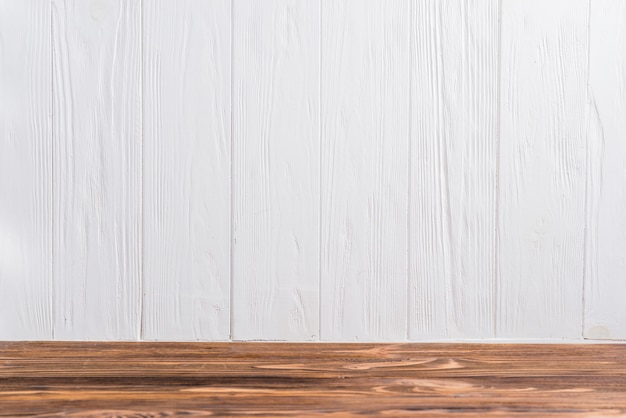 An empty wooden desk against white painted wall