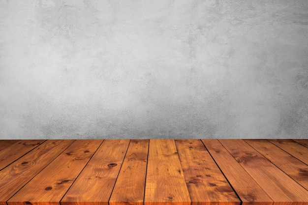 Empty wooden desk table top on wood with cement wall background.