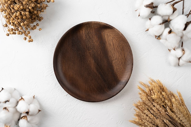 Empty wooden dish on a table background with a cotton branch and wheat  menu card for restaurants