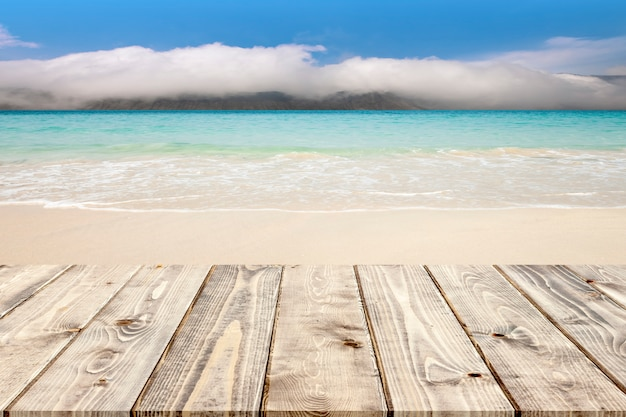 Empty wooden floor on tropical white sand beach and foggy mountain background.