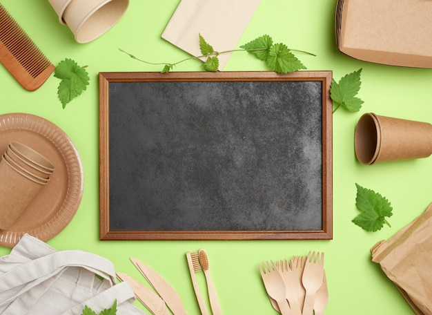 Пустой деревянный каркас и одноразовые бумажные тарелки, чашки, деревянные вилки на зеленом фоне
