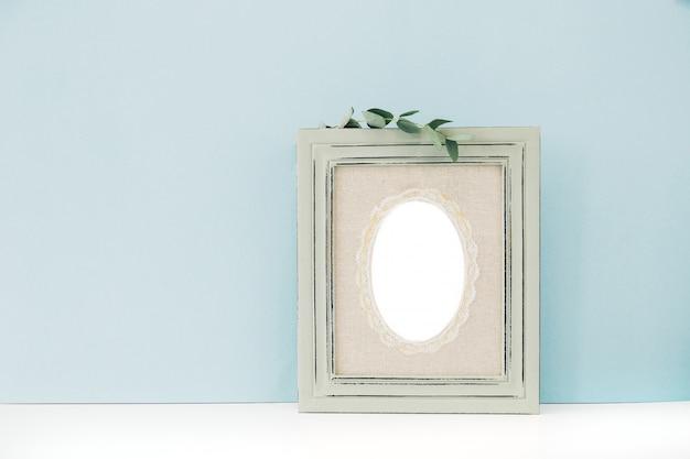 Опорожните деревянную рамку и евкалипт в вазе на таблице на сини. макет