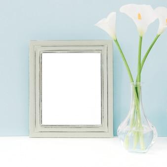 Опорожните деревянную рамку и цветки в вазе на таблице на сини. макет