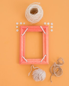 An empty wooden frame decorated with button and spools on an orange backdrop