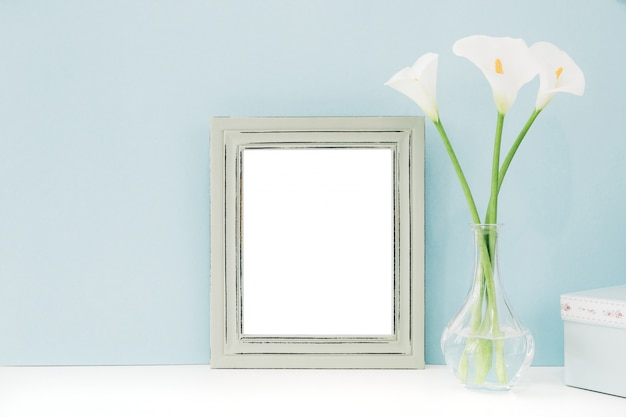 Empty wooden frame and flowers in vase on table on blue background.