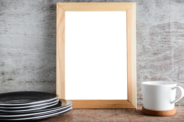 Empty wooden frame and kitchen accessories on the table