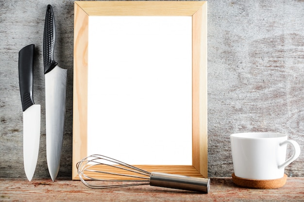 An empty wooden frame and kitchen accessories on a wooden background