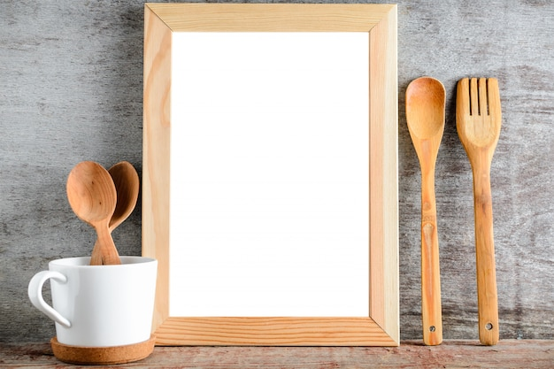 Empty wooden frame and kitchen utensils on a wooden table