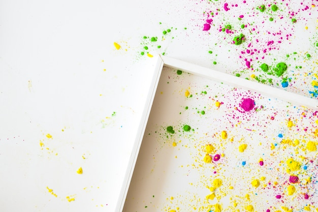 An empty wooden frame on white backgrounds with holi color powder