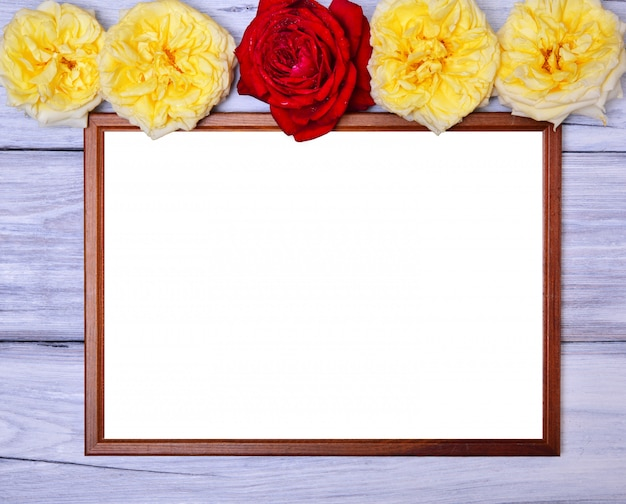 Empty wooden frame on a white wooden background, at the top of the buds of flowering roses