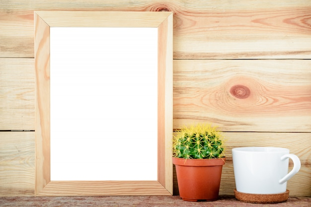 Empty wooden frame with cactus and white cup on wooden background