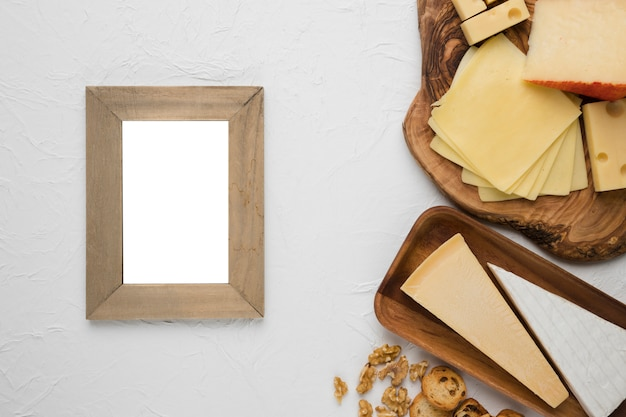 Empty wooden frame with cheese platter and ingredient on white surface
